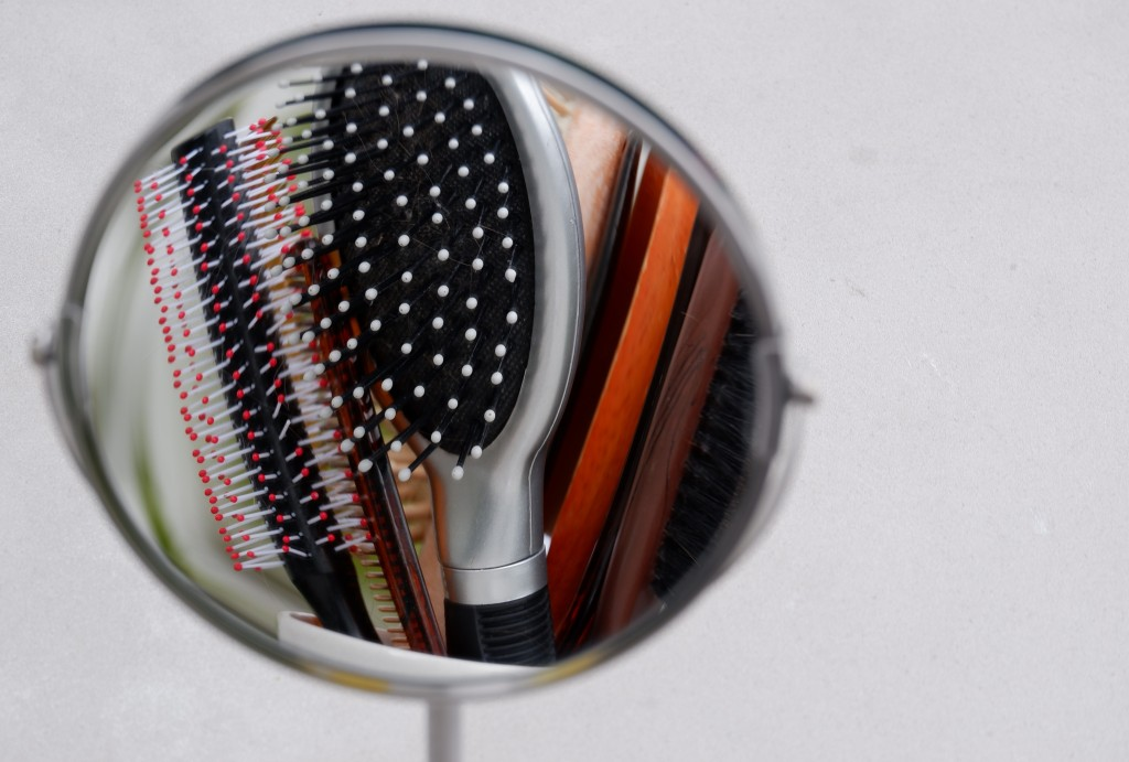 Haarborstels in de make-up spiegel. Hairbrushes in mirror Fotografie